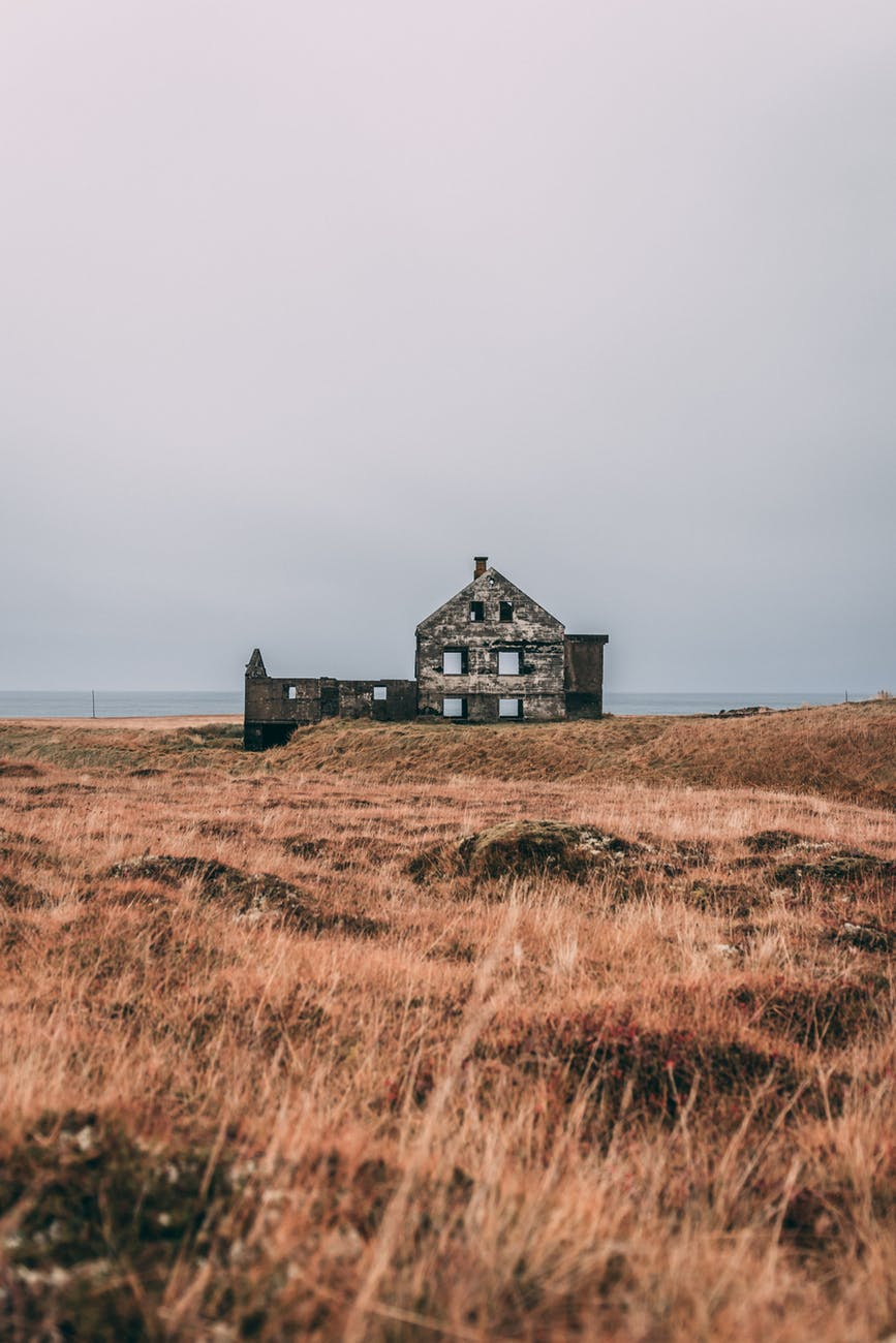 gray concrete house in brown field